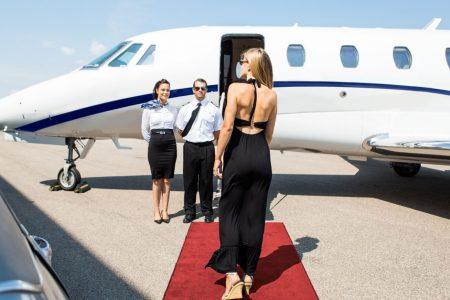 une femme marche sur le tapis rouge en direction d'un jet privée