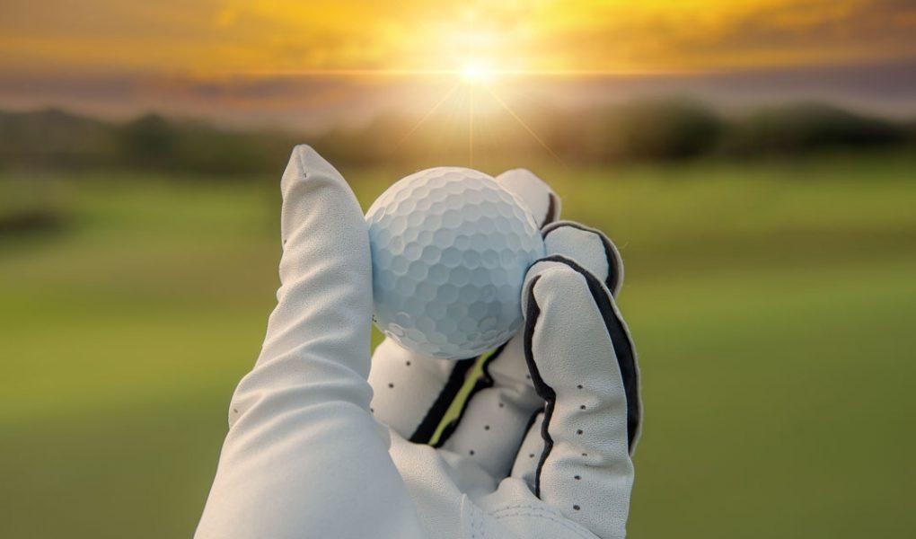 une main tenant une balle de golf devant un couché de soleil